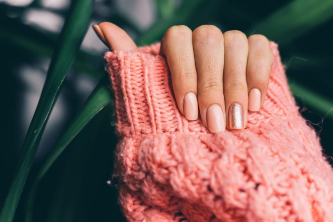 Pretty nude color manicure, one finger shiny golden, on knitted pink wool pillover background