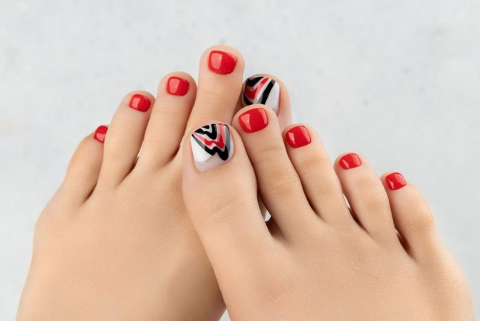 Womans feet and hands on gray background. Beautiful summer red nail design